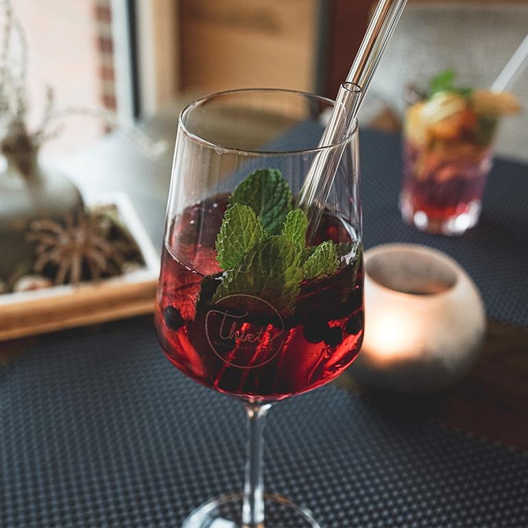 Rotes Getränk mit Glasstrohhalm